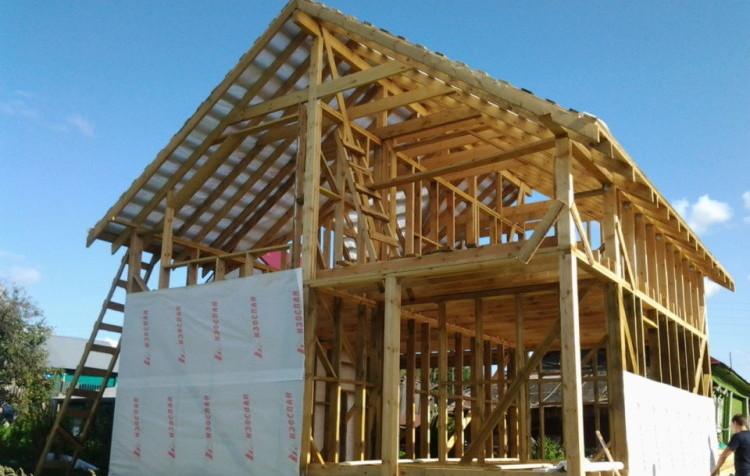 процесс утепления каркасного дома с укладкой утеплителя между несущими конструкциями