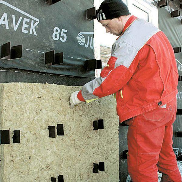 Нанизывание минеральной ваты на кронштейн навесной фасадной системы